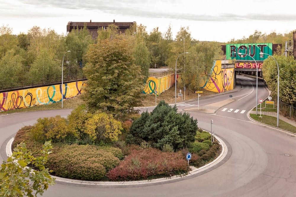 L'habillage de pont, par Sascha Di Giambattista, qui veut ancrer le nom de «Rout Lëns» dans l'imaginaire des gens, surplombe la fresque murale d'Eric Mangen, qui illustre l'idée de mouvement, de transformation et de transition. (Photo: Boris Loder)